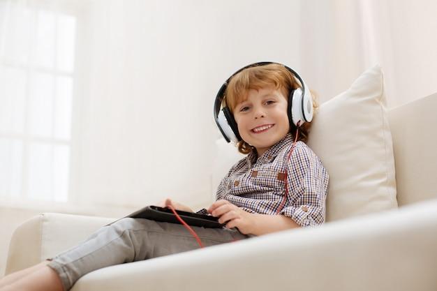 Criança adorável e inteligente usando seu gadget para ouvir algumas músicas enquanto está sentado em um sofá e usando fones de ouvido