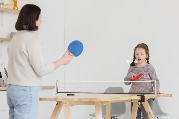 Criança adorável e mãe brincando dentro de casa