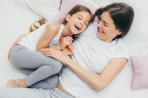 Criança adorável e sua mãe se divertem juntos na cama, fazem cócegas, sorriem alegremente, brincam depois de dormir bem