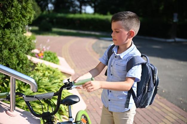 Criança adorável estacionando sua bicicleta na entrada da escola. garoto bonito voltando para a escola