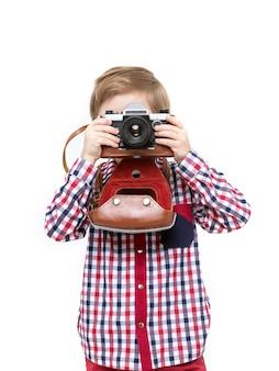 Criança adorável fotógrafo inteligente, segurando a câmera preta nas mãos