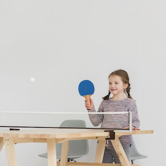Criança adorável jogando pingue-pongue dentro de casa