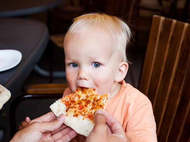 Criança adorável menino comendo uma fatia de pizza em um restaurante no verão, olhando para a câmera