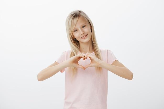 Criança adorável mostrando gesto de coração e sorrindo