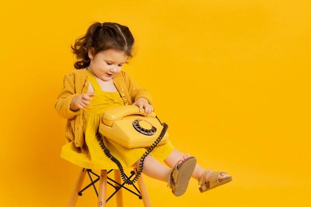 Criança adorável posando enquanto segura o telefone