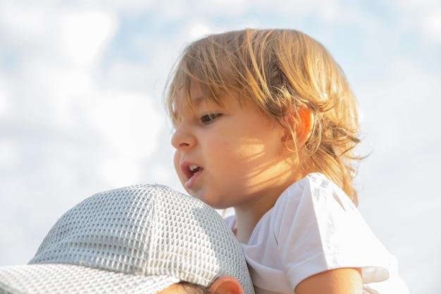 Criança adorável sentada nos ombros do pai, retrato de uma criança sentada no pescoço do pai