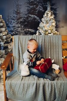 Criança adorável sorridente, sentado no banco com muitos presentes de natal