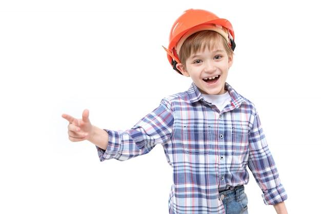 Criança adorável, vestida como capataz de capacete e camisa laranja