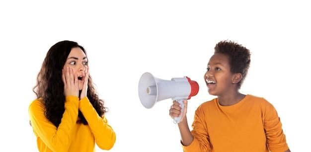 Criança africana com um megafone e uma adolescente atônita isolada em um branco