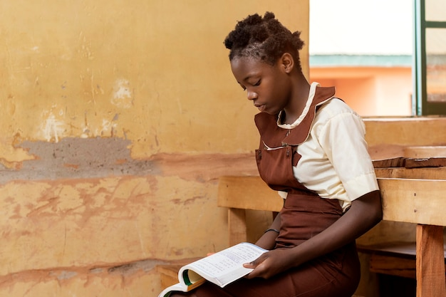 Criança africana inclinando-se na aula