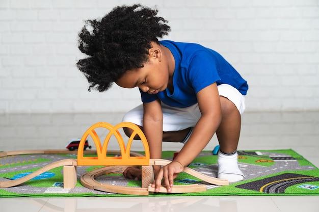 Criança afro-americana brincando com seus brinquedos de carro em casa