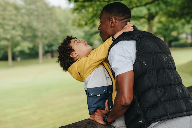 Criança afro-americana e seu pai brincando no parque