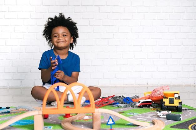 Criança afro-americana feliz comendo pizza na mesa