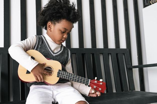 Criança afro-americana feliz tocando ukulele em casa