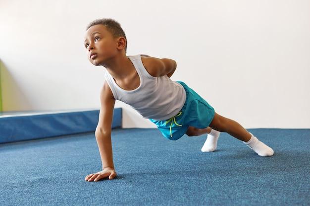 Criança afro-americana magra e disciplinada em roupas esportivas fazendo prancha com um braço