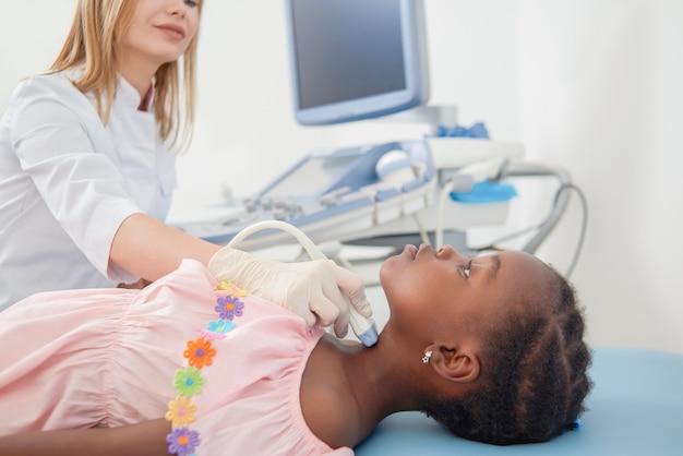 Criança afro, mentindo quando médico varrendo o pescoço dela.