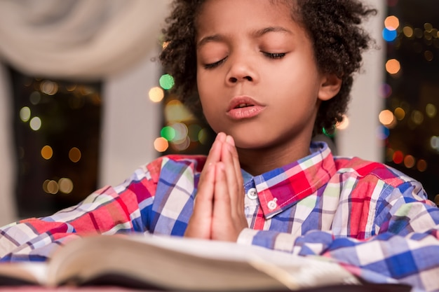 Criança afro orando. criança negra reza ao lado da janela. oração da noite do menino. gesto de fé.