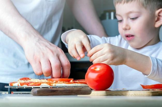 Criança ajuda seu pai a cozinhar pizza caseira