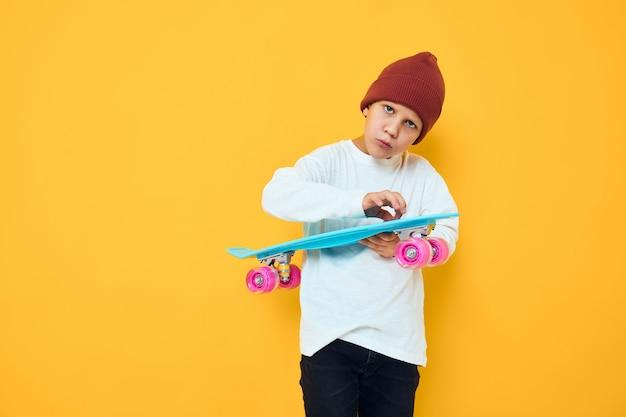 Criança alegre, casual skate azul fundo de cor amarela