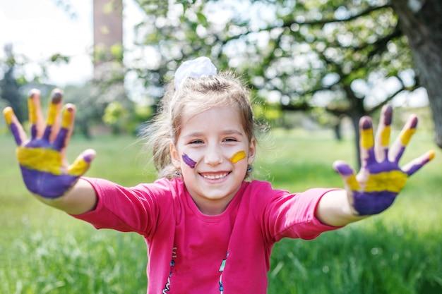 Criança alegre com as mãos em uma tinta.