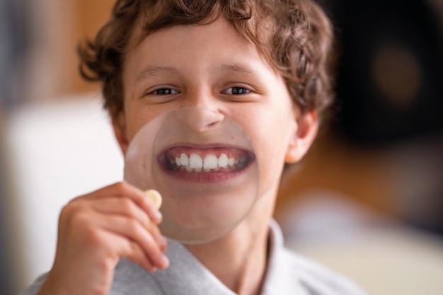 Criança alegre com óculos mostra dentes brancos no copo de uma grande lupa