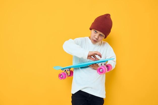 Criança alegre com um skate de chapéu vermelho no estúdio de mãos posando