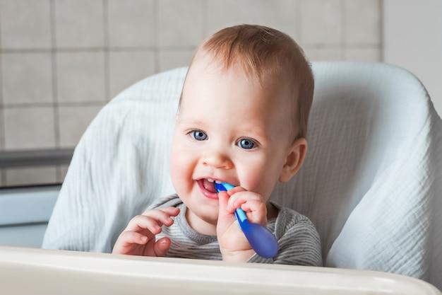 Criança alegre come comida com colher. feche o retrato do menino feliz na cadeira alta. alimentando