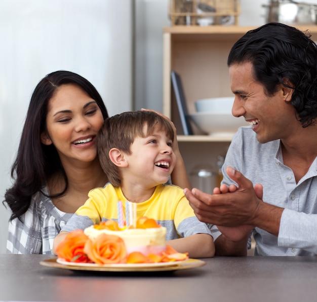 Criança alegre comemorando seu aniversário com seus pais