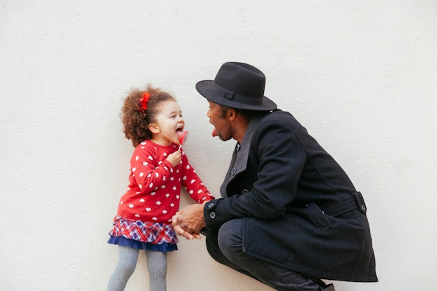 Criança alegre, degustação de um doce pirulito