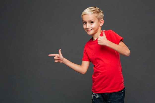 Criança alegre do rapaz pequeno que aponta mostrando os polegares acima.