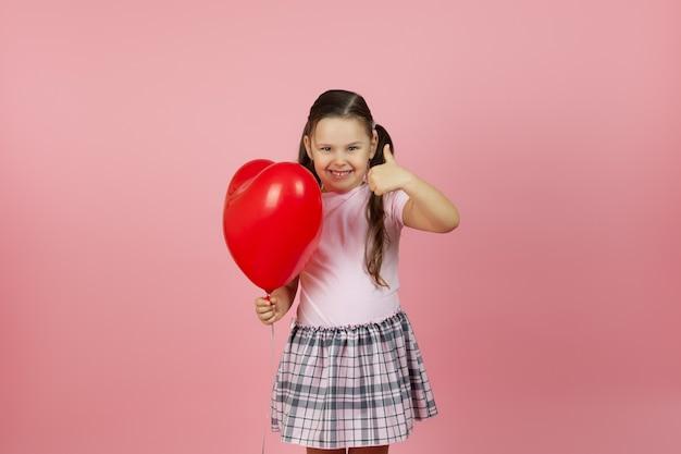 Criança alegre e alegre segurando um balão vermelho em forma de coração e fazendo sinal de positivo