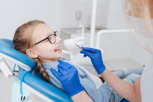Criança alegre e inteligente visitando o dentista para exames regulares e sorrindo para demonstrar um dispositivo especial de fixação nos dentes