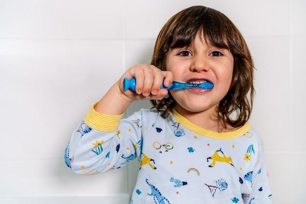 Criança alegre escovando os dentes de pijama antes de dormir