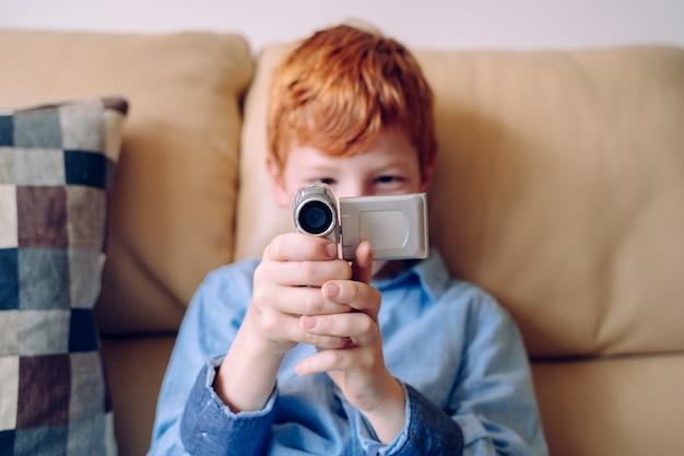 Criança alegre gravação com uma câmera de vídeo em casa. expressão artística e atividades de aprendizagem para o crescimento educacional de crianças