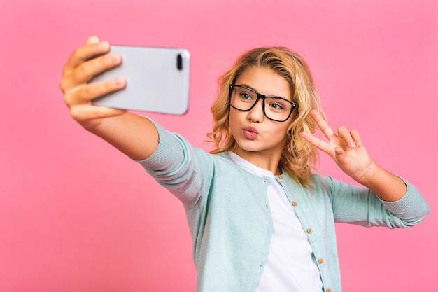 Criança alegre modelo de cabelo ondulado se divertir em uma viagem de lazer, fazer uma videochamada de selfie, usar um pulôver elegante