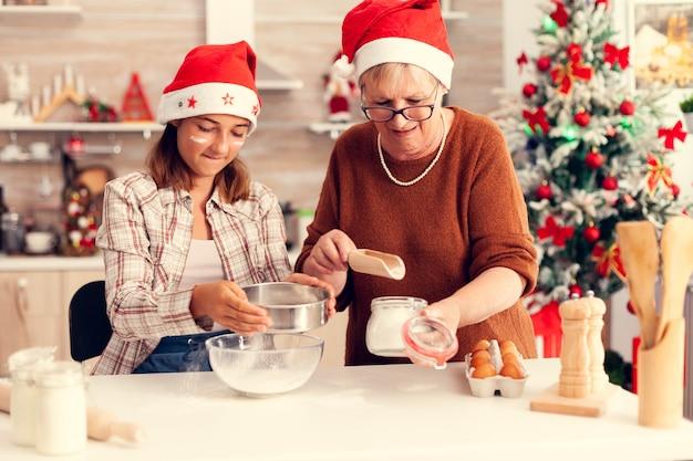 Criança alegre na cozinha no dia de natal com a árvore de natal