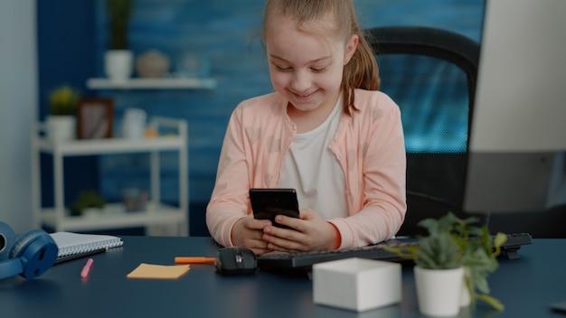 Criança alegre olhando para smartphone com tela de toque