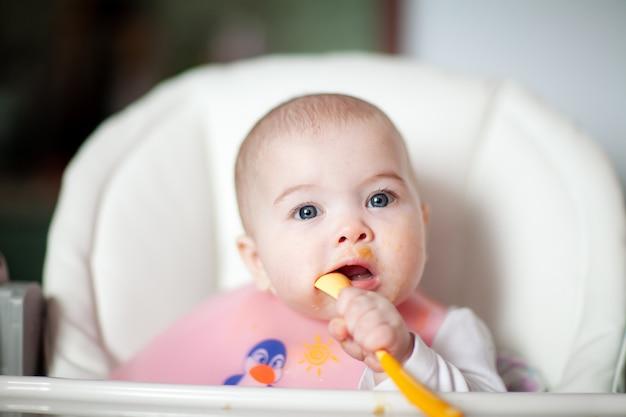 Criança alegre se alimenta com uma colher. retrato de menina criança feliz na cadeira alta
