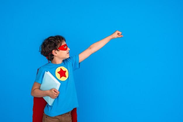 Criança alegre, vestida com traje de super-heróis segura o livro e estende a mão