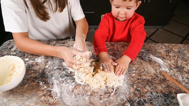 Criança amassando massa com as mãos na cozinha