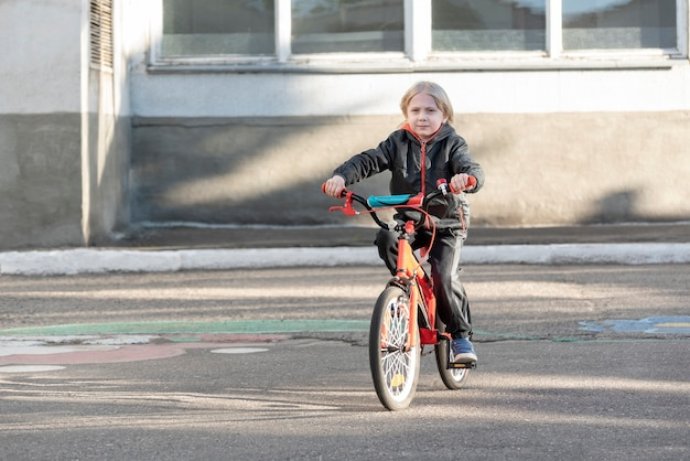 Criança anda de bicicleta em estrada pavimentada. menino aprende a andar de bicicleta.