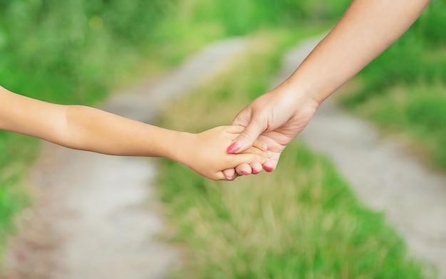 Criança anda de mãos dadas com sua mãe