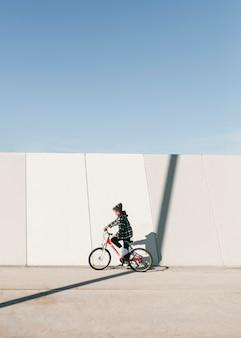 Criança andando de bicicleta ao ar livre com espaço de cópia