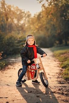 Criança andando de bicicleta em agasalhos no outono Foto Premium