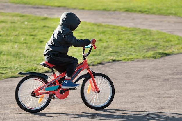 Criança andando de bicicleta. menino aprendendo a andar de bicicleta.