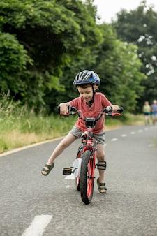 Criança andando de bicicleta na ciclovia na chuva. criança com capacete aprendendo a andar no verão. garoto feliz andando de bicicleta, se divertindo ao ar livre na natureza. esporte ativo, lazer familiar