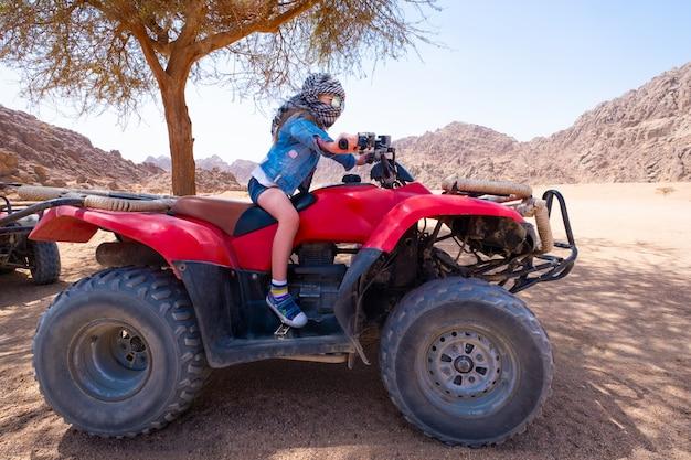 Criança andando de moto-quatro no deserto