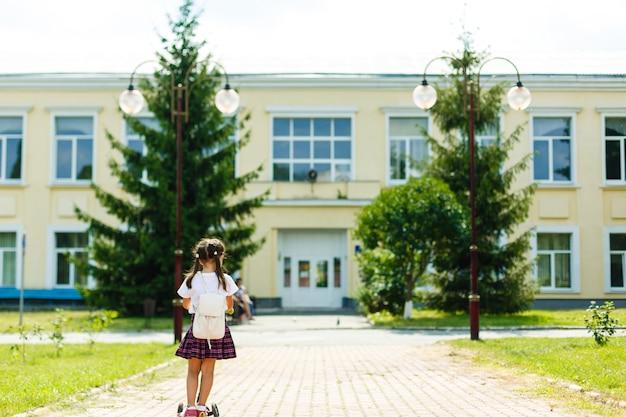 Criança andando de scooter no caminho de volta à escola