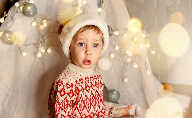 Criança animada segurando um presente perto da árvore de natal. retrato de menino feliz