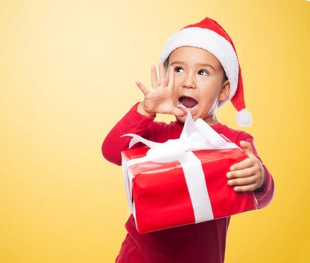 Criança animado com a mão ao lado de sua boca